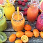 Auf dem Bild sind vier Smoothies in Gläsern zu sehen. Es sind ein grüner, ein gelber, ein orangener, ein dunkelorangener und ein lilaner Smoothie zu sehen. Neben den Gläsern liegt verschiedenes Obst, wie Kiwis, Orangen, Blutorangen und Himbeeren.