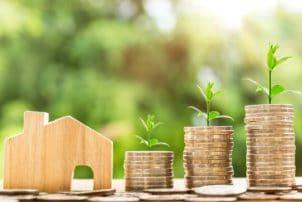 Auf dem Bild ist ein kleines Holzhaus zu sehen. Neben dem Haus sind Münzhaufen, aus welchem Pflanzen wachsen.