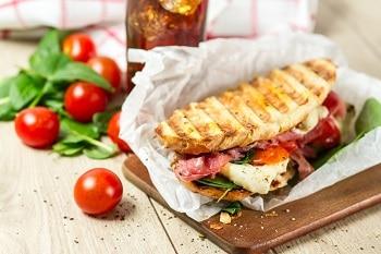 auf diesem bild ist ein Panini zu sehen, welches kross getoatet wurde und apetitliche Grillstreifen hat. Es ist reichlich belegt mit Schinken, Salami, Salat und Käse.