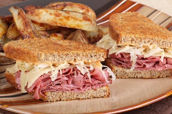 Zwei Sandwiches mit Pastrami und Käse auf einem Teller. Daneben Kartoffelecken.