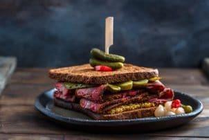 Ein Sandwich bestehend aus Toastscheiben, Pastrami und Gewürzgurken. Auf dem Toast liegen weitere Gewürzgurken. Das Sandwich ist mit einem Holzspieß fixiert.