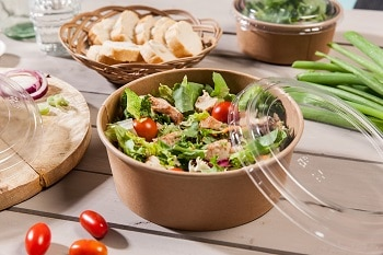 Auf dem Bild ist ein Salat in einer Kartonschale zu sehen. Der Salat besteht aus Rucola, Salatblättern, Tomaten und Hühnchen. Auf der Schale liegt ein aus Kunststoff bestehender Deckel. Im Hintergrund sind eine Schale mit Brot, so wie verschiedenstes Gemüse zu sehen.