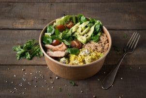 Auf dem Bild ist ein Salat in einer Kartonschale von Bionatic zu sehen. Der Salat besteht unter anderem aus Tomaten, Salatblättern, Fleisch und Gurken.
