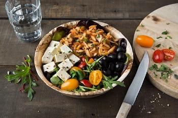 Auf dem Bild ist eine Salatschale aus Palmblatt zu sehen. In der Schale befinden sich Tomaten, Reis, Fetakäse, , Rucola und Oliven. Neben der Schale liegt ein Messer und ein Glas Wasser.