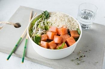 Auf dem Bild ist eine Schale aus Zuckerrohr zu sehen, in welcher sich Reis, Lachs und Salat befinden. Die Schale steht auf einem Holzbrett, auf welchem sich ebenfalls zwei Essstäbchen und ein Glas Wasser befinden.