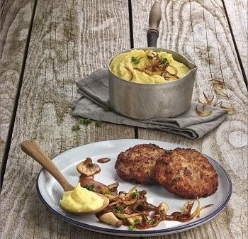 Zwei Frikadellen von Salomon auf einem Teller. Ebenfalls auf dem Teller liegen pilze und ein Holzlöffel mit Kartoffelbrei. Im Hintergrund ist ein Topf mit Kartoffelbrei zu sehen.