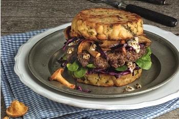 Ein Burger von Salomon mit Knödeln als Buns, belegt mit Salat, Pilzen und einer Bulette.