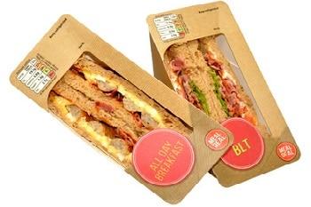 Zwei Sandwiches in einer typischen dreieckigen Sandwichverpackung. Ein Sandwich ist mit Speck, Salat und Tomaten belegt, das andere mit Speck und Ei