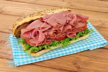Ein Sandwich mit Salat und Scheibenweise Pastrami, liegend auf einer Servierte auf einem Holztisch.