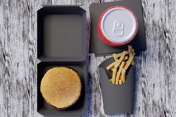 Schwarze Karton Verpackungen. Ein Burger in einem Burgerkarton, Pommes in einer Pommesverpackung und ein Getränk auf einer schwarzen Pappe.