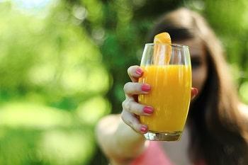 Eine Frau die einen Glas Orangensaft in der Hand hält. Am Rand des Glases hängt eine Orangenscheibe.