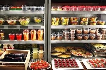 Ein Supermarkt Kühlregal mit vielen Produkten in Plastikverpackungen. Unter den Produkten sind Salate, Pizzen, Shakes und süße Backwaren.