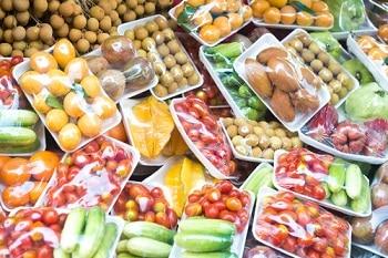 Verschiedenes Obst in Plastikverpackungen. Unter anderem sind Gurken, Tomaten und Orangen zu sehen.