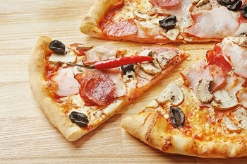Ein Stück einer Pizza belegt mit Salami, Schinken und Pilzen auf einem Holzbrett.