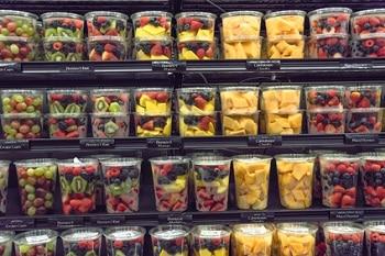 Ein Regal befüllt mit Plastikbechern, in denen sich frisches, geschnittenes Obst befindet. Es sind Becher mit Kiwis, Mangos und gemischten Beeren zu sehen.