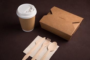Ein to go Kaffeebecher, eine geschlossene Kartonverpackung und Löffel, Messer und Gabel auf einer Servierte.