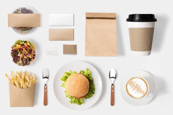 Ein Salat in einer Schale, Pommes in einer Papiertüte, ein Teller mit einem Burger, daneben Gabel und Löffel. Eine Tasse mit Kaffee, ein Kaffee to go Becher, eine Papiertüte und weitere Verpackungen aus Papier.