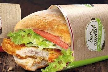 Ein Baguette belegt mit Salatblättern, Tomaten und Hühnchen, welches in einer Papiertüte von Weber eingepackt ist.