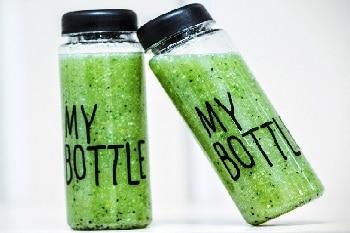 """Zwei grüne Smoothies, die in Glasflaschen sind. Auf den Flaschen steht """"MY BOTTLE""""."""