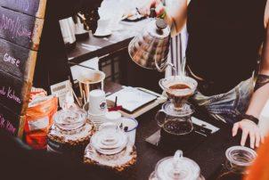 Eine Frau die Wasser aus einer Kanne in eine Kaffeemaschine füllt. Es ist eine Theke eines Cafés zu sehen.