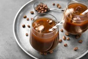 Gläser mit Cold Brew Coffee und Kaffebohnen daneben