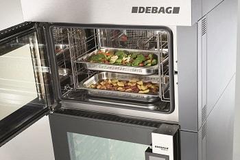 DEBAG Multifunktionsöfen. Auf dem Bild ist ein Debag Backofen zu sehen, der offen steht und in dem zwei GN Bleche sind. Eines mit Gemüse befüllt, das zweite mit Kartoffeln belegt.