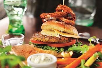 Ein Burger von FINDUS belegt mit veganem Käse, einer Falafel Bulette, Petersilie, Knochblauch, Tomaten und Salat, der auf einem Holzbrett steht. Im Vordergrund sind verschwommen Süßkartoffelpommes und eine Schale mit Sour Cream zu sehen.
