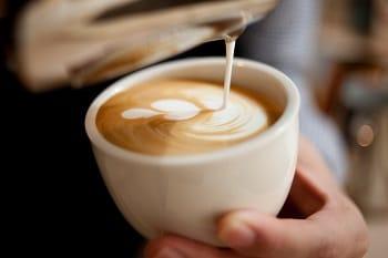 Ein Kaffee Latte in einer Tasse, dessen Milch gerade eingegossen wird.