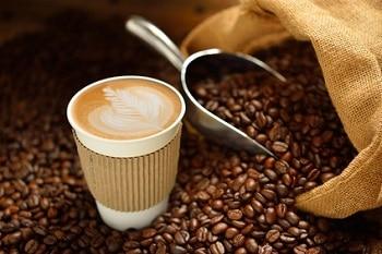 Ein Kaffee in einem Becher inmitten von Kaffeebohnen. Daneben ein Sack mit Kaffeebohnen und einer Kaffeekelle