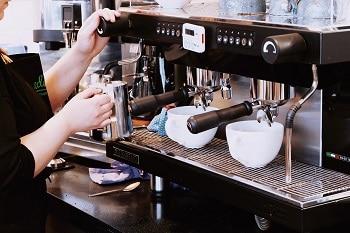 Zwei Kaffeetassen, die an einer Kaffeemaschine stehen. Eine Frau bedient diese Kaffeemaschine.