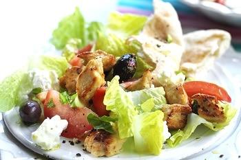Vegetarisches Geschnetzeltes von Quorn auf einem Teller zusammen mit Salat, Tomaten, Oliven und Fetakäse.
