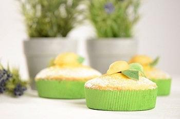 Drei Muffins eingehüllt in grünen Backformen.