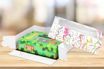Ein Kuchen mit grüner Glausur der von einer RAUSCH Verpackungen umgeben ist, dessen Deckel ein Sichtfenster hat.