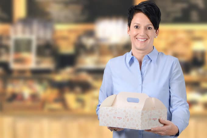 Eine Frau mit blauer Bluse, die eine Transport Verpackung für Backwaren von RAUSCH in den Händen hält.