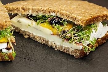 Schwarzbrot mit Camembert, honig senf, sprossen, salat und preiselbeeren belegt. gezeigt an der Schnittkante vegetarisch und vegan