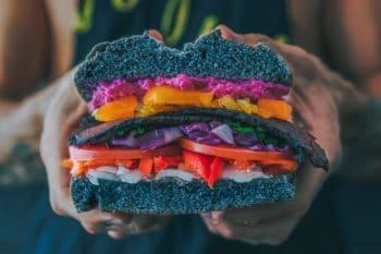 Burger mit schwarzem Bun und Gemüse in der Hand