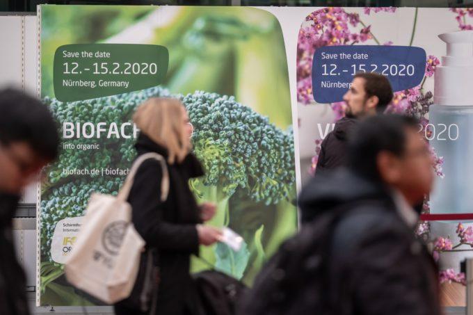 Biofach Menschen laufen an Plakat vorbei