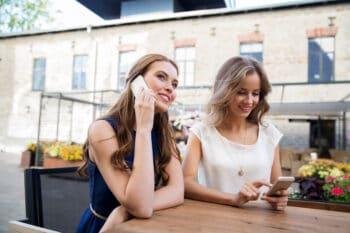 Zwei Frauen im Cafe mit Handy in der Hand