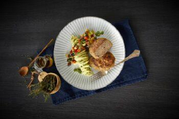 Nudelgericht mit Geflügelhacksteak auf einem Teller