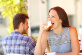 Eine Frau isst ein Sandwich als Snack