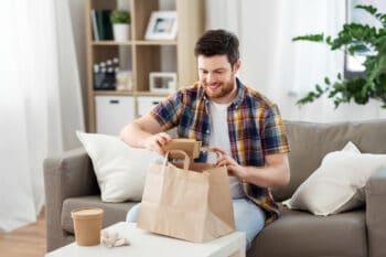 Mann holt Essen in nachhaltiger Vepackung aus Papiertüte