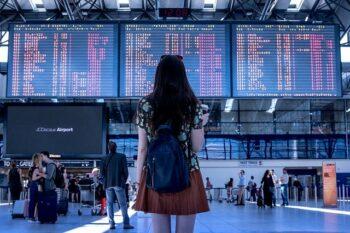 Frau steht im Flughafen vor Flugtabelle