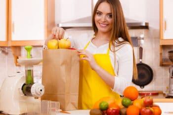 Eine Frau packt Apfel aus der Papiertüte aus