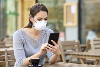 Frau sitzt mit Maske im Cafe