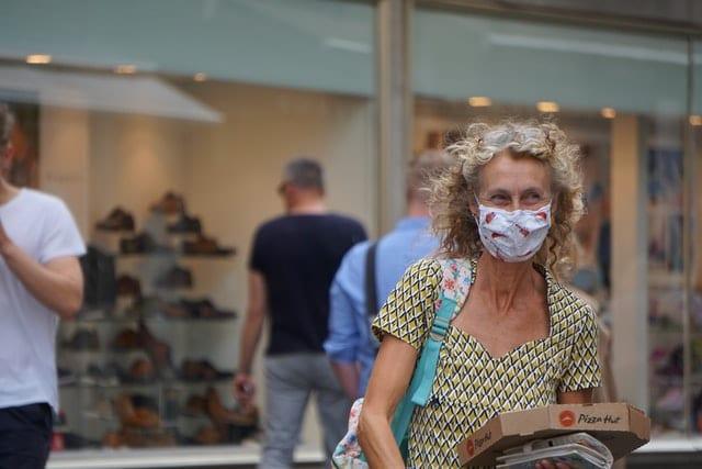 Frau mit Maske und Pizza To Go