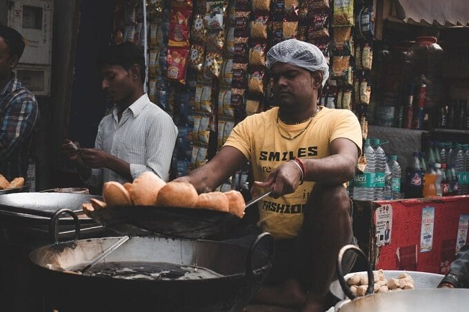 Indischer Verkäufer frittiert Teigbällchen