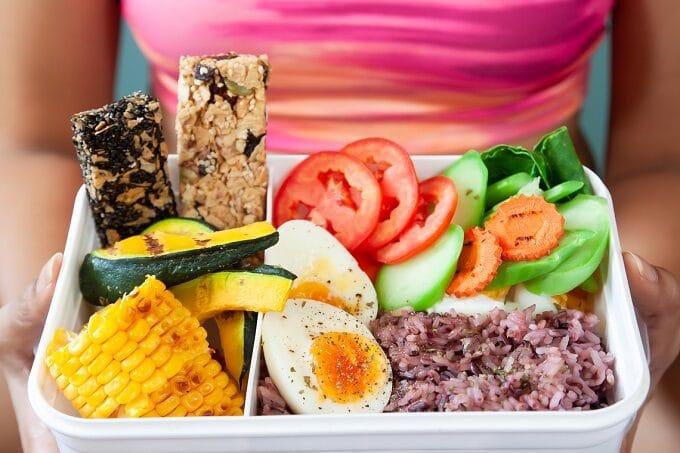 Gesunde Lunchbox mit Gemüse wie Avocado, Mais und Eier