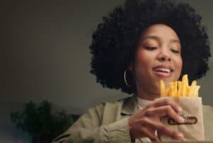 Frau mit Pommes Frites in der Hand