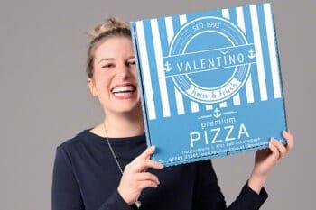 Frau hält Pizzakarton