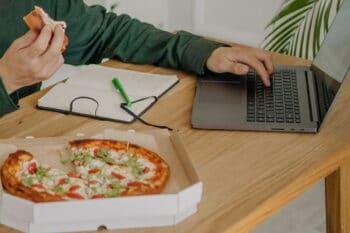 Pizza im Karton auf einem Schreibtisch im Homeoffice / snackconnection